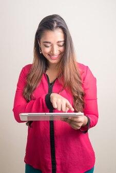 Retrato de uma jovem e bonita mulher de negócios indiana feliz usando tablet digital