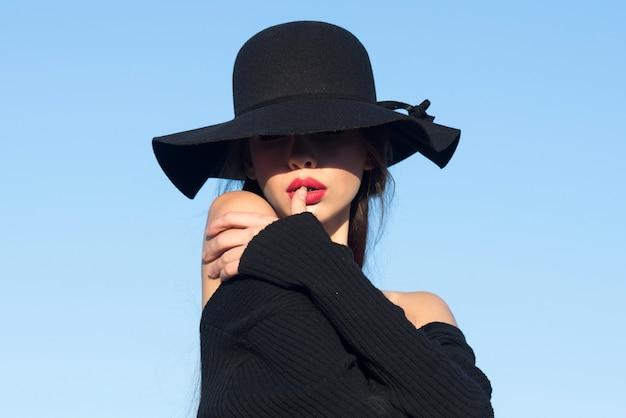 Retrato de uma jovem e bonita mulher elegante vestindo acessórios elegantes olhos escondidos com chapéu romântico modelo mulher com rosto sensual luz e sombra