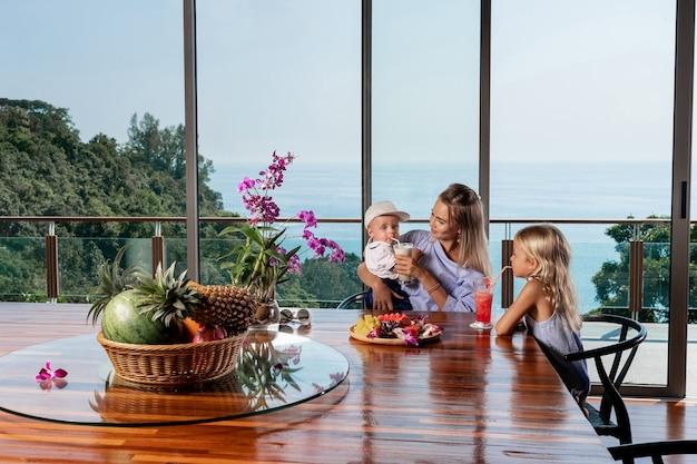 Retrato de uma jovem e linda família caucasiana mãe e seus dois lindos filhos sentados à mesa da cozinha em casa e tomando café da manhã juntos. férias de verão
