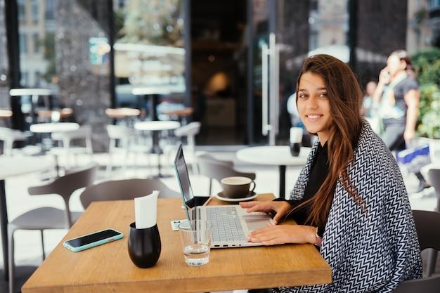 Retrato de uma jovem e linda mulher trabalhando em um computador portátil, encantadora aluna usando netbook enquanto está sentado no café