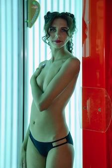 Retrato de uma jovem elegante bonita desfrutando de um bronzeado no solário moderno. mulher jovem e saudável no solário vertical, obtém prazer e goza. conceito de estilo de vida saudável e pele bonita e bem cuidada