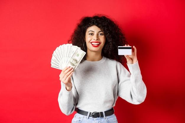 Retrato de uma jovem elegante com cabelo encaracolado, mostrando dinheiro em dinheiro e cartão de crédito plástico, fundo vermelho.