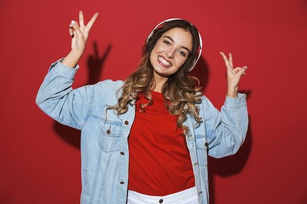 Retrato de uma jovem elegante e alegre, vestindo uma jaqueta jeans isolada na parede vermelha, ouvindo música com fones de ouvido, dançando