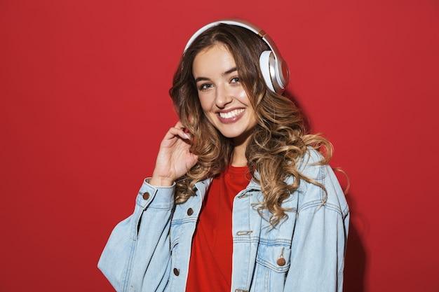 Retrato de uma jovem elegante e alegre, vestindo uma jaqueta jeans isolada na parede vermelha, ouvindo música com fones de ouvido