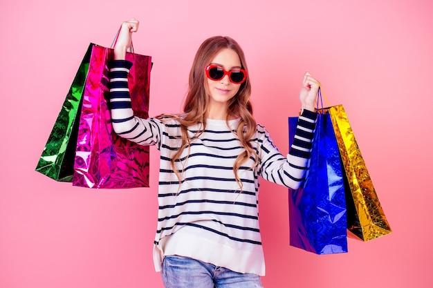 Retrato de uma jovem elegante e atraente com um suéter listrado e óculos de sol vermelhos, sorrindo e segurando um monte de sacolas de compras em um fundo rosa no estúdio. conceito de shopaholism e vendas
