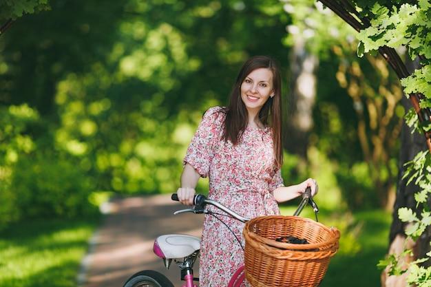 Retrato de uma jovem elegante em um vestido floral rosa longo, pare de andar sob o arco de carvalho em uma bicicleta com uma cesta para compras, comida ou flores ao ar livre, tempo de recreação feminino bonito na primavera ou no parque de verão