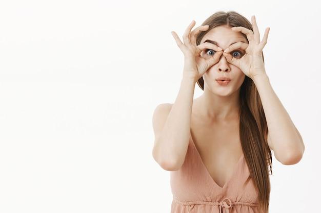 Retrato de uma jovem elegante, intrigada e satisfeita em um vestido bege, fazendo círculos sobre os olhos como se estivesse olhando através de binóculos em grandes liquidações, impressionado