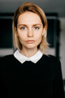 Retrato de uma jovem elegante loira de cabelos curtos com roupas pretas formais, posando dentro de casa