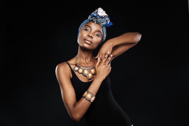 Retrato de uma jovem elegante posando e olhando para a frente no estúdio isolado na parede preta