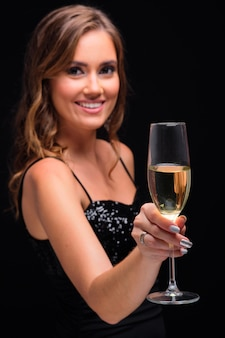 Retrato de uma jovem elegante, segurando o copo com champanhe.