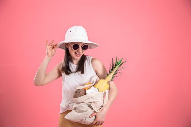 Retrato de uma jovem elegante vestida com roupas de verão, com um chapéu e óculos escuros, segurando uma sacola de frutas ecológicas, na rosa isolada.