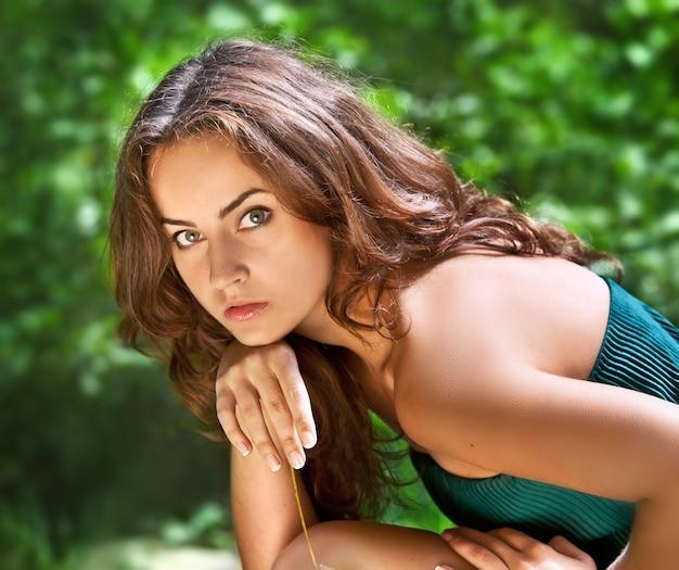 Retrato de uma jovem em fundo de floresta manchada