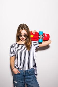 Retrato de uma jovem em óculos de sol posando com skate em pé sobre uma parede branca