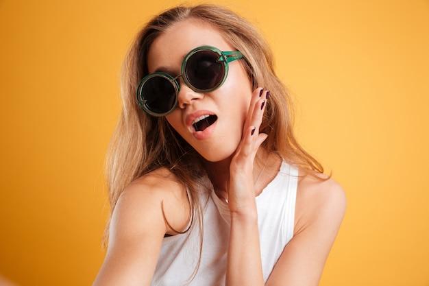Retrato de uma jovem em óculos de sol, tomando uma selfie
