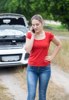 Retrato de uma jovem em pé no carro quebrado e falando ao telefone