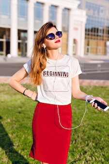 Retrato de uma jovem em pé segurando um smartphone e ouvindo música em fones de ouvido