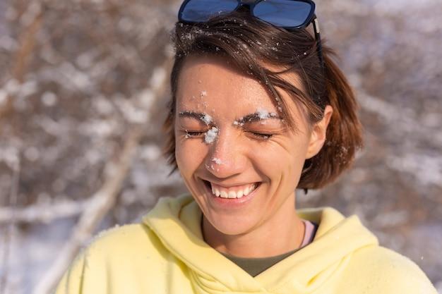 Retrato de uma jovem em uma floresta de inverno em um dia ensolarado com um sorriso branco como a neve, brincando