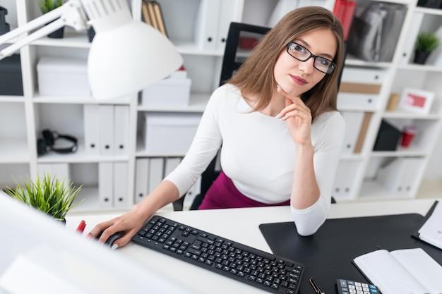 Retrato de uma jovem em uma mesa de computador no escritório.