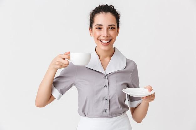 Retrato de uma jovem empregada sorridente, vestida de uniforme