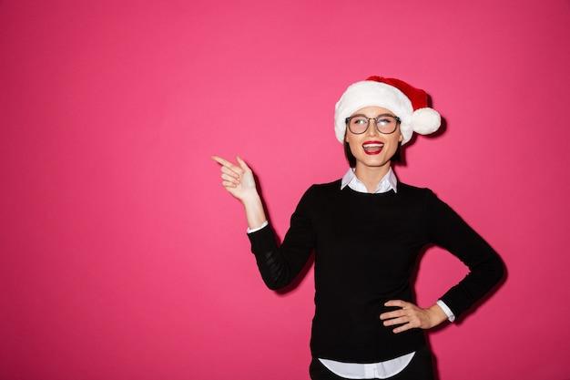 Retrato de uma jovem empresária alegre com chapéu de papai noel