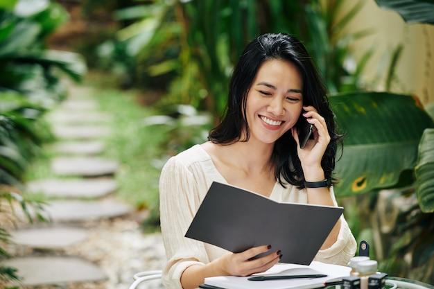 Retrato de uma jovem empresária alegre lendo catálogo e pedindo ingredientes para a marca de cosméticos em que está trabalhando
