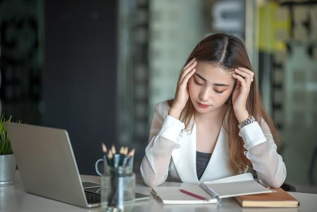 Retrato de uma jovem empresária asiática cansada, sentada à mesa com o laptop no escritório