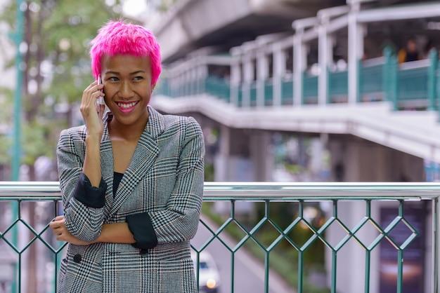 Retrato de uma jovem empresária asiática rebelde com cabelo rosa em uma ponte pedonal na cidade ao ar livre