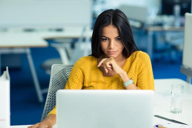 Retrato de uma jovem empresária casual de suéter usando um laptop no escritório