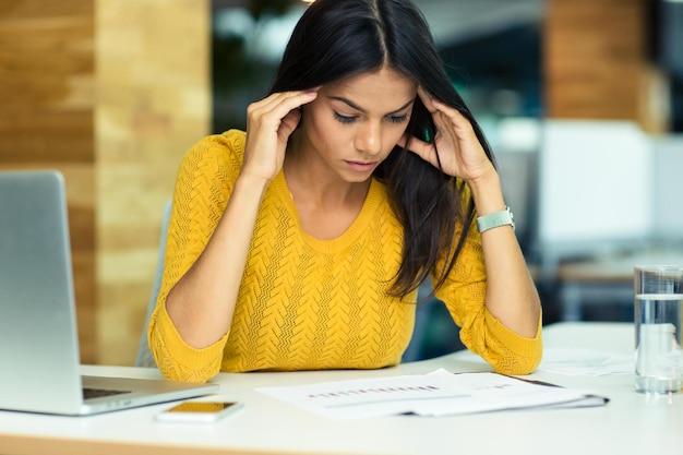 Retrato de uma jovem empresária casual lendo documentos no escritório