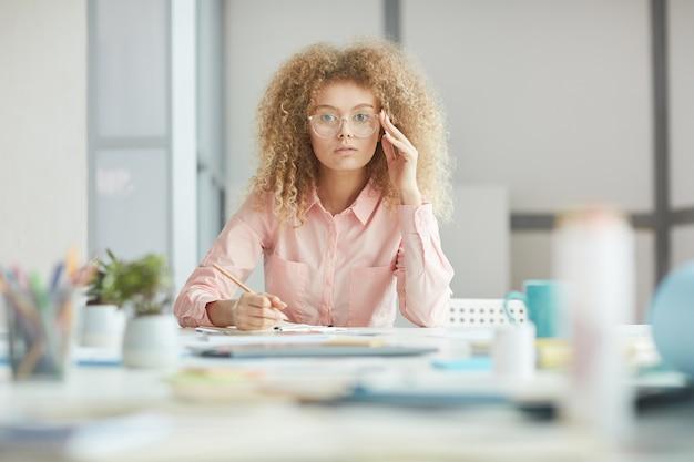 Retrato de uma jovem empresária descolada usando óculos enquanto trabalha ou estuda na mesa na sala branca, copie o espaço
