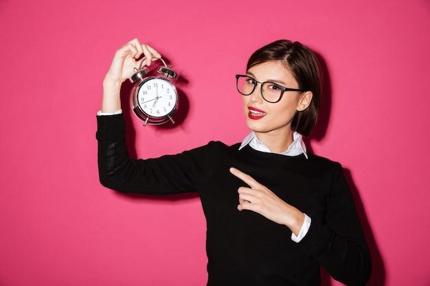 Retrato de uma jovem empresária feliz, apontando para o relógio despertador