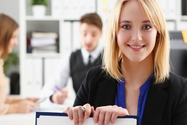 Retrato de uma jovem empresária no escritório contra colegas