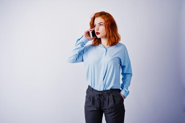 Retrato de uma jovem empresária ruiva de camisa azul e calça falando ao telefone.