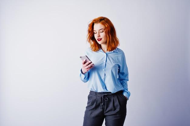 Retrato de uma jovem empresária ruiva de camisa azul e calça mandava um sms no telefone.