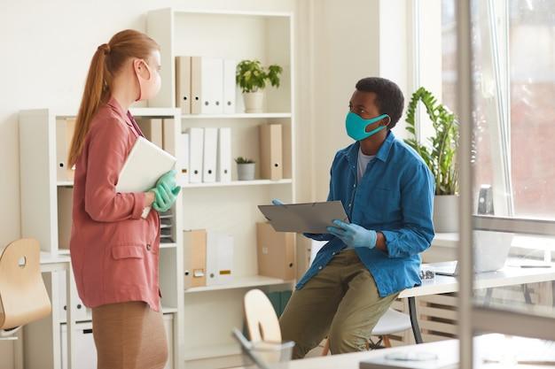 Retrato de uma jovem empresária usando máscara e luvas, conversando com um colega afro-americano enquanto trabalhava em um escritório pós-pandemia
