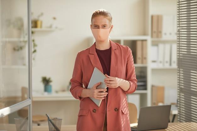 Retrato de uma jovem empresária usando máscara e luvas em pé no local de trabalho em escritório pós-pandemia