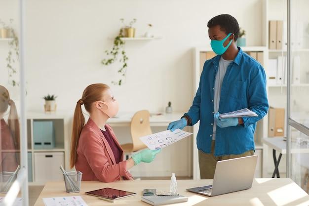 Retrato de uma jovem empresária usando máscara e luvas, entregando documentos a um colega afro-americano enquanto trabalhava em um escritório pós-pandêmico