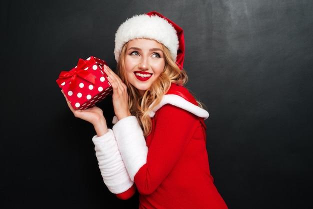 Retrato de uma jovem encantadora alegre com chapéu de papai noel segurando uma caixa de presente sobre uma superfície preta