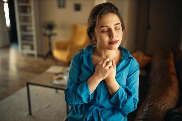 Retrato de uma jovem encantadora alegre sentada no sofá na sala de estar fechando os olhos, mantendo as mãos no peito, orando, tendo uma expressão facial calma e pacífica, sonhando com algo agradável