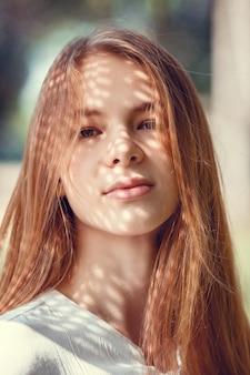 Retrato de uma jovem encantadora ao ar livre. luz e sombra. retrato interessante do rosto de uma jovem coberto por uma sombra incomum