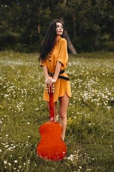 Retrato de uma jovem encantadora, apoiado em um violão e desviar o olhar ao ar livre. jovem freelancer fazendo conteúdo para seu canal em um campo e com um violão.