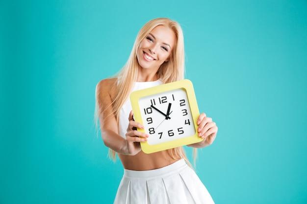 Retrato de uma jovem encantadora com cabelo comprido, mostrando o relógio de parede em mãos isoladas sobre o fundo azul.