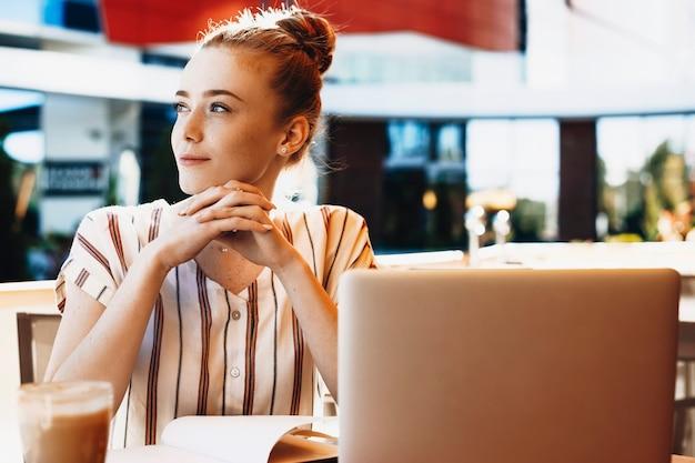 Retrato de uma jovem encantadora com cabelo ruivo e sardas, inclinando a mão nas mãos dela, olhando para longe enquanto freelancer lá fora bebendo café.