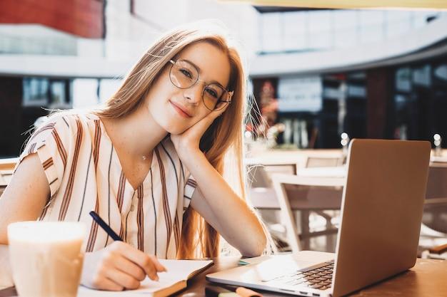 Retrato de uma jovem encantadora com cabelo ruivo e sardas, olhando para a câmera enquanto trabalhava em seu laptop lá fora, bebendo café.