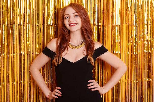 Retrato de uma jovem encantadora com lábios vermelhos e longos cabelos vermelhos, sorrindo para a câmera com enfeites dourados no espaço, mantendo a mão dos quadris do filho