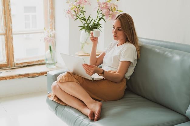 Retrato de uma jovem encantadora com laptop trabalhando em casa enquanto está sentado no sofá