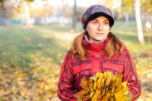 Retrato de uma jovem encantadora com uma jaqueta vermelha caminhando no parque outono com um buquê de folhas de bordo amarelas