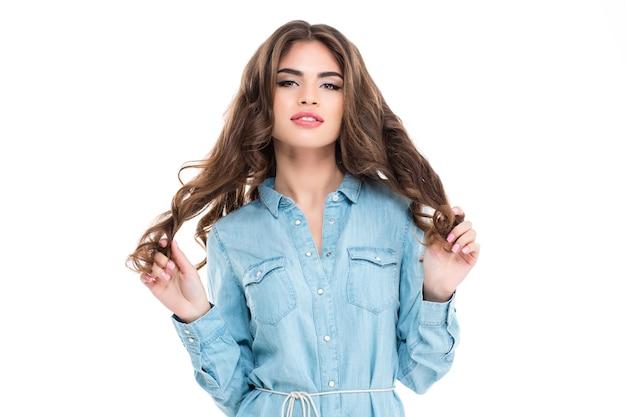 Retrato de uma jovem encantadora e sensual em uma camisa jeans azul sobre uma parede branca.