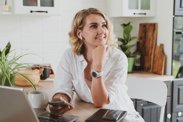 Retrato de uma jovem encantadora em fones de ouvido com laptop trabalhando em casa na cozinha