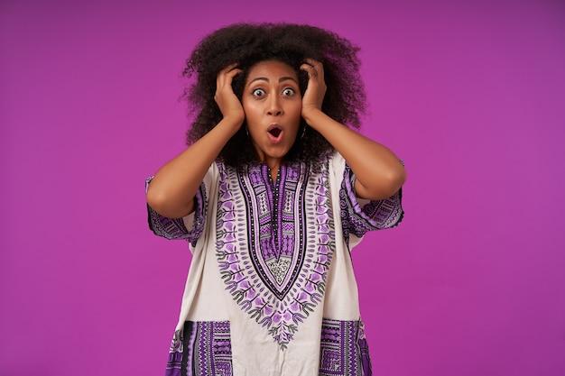 Retrato de uma jovem encaracolada surpresa com penteado casual segurando sua cabeça com as mãos levantadas com rosto surpreso, olhos arredondados e sobrancelhas levantadas em roxo